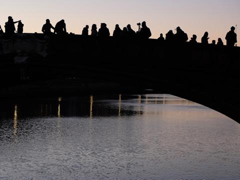 Toeristen verzamelen zich op een brug over de Arno